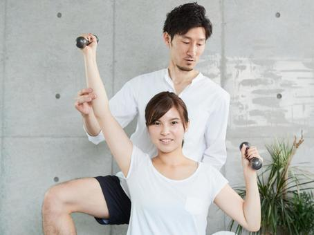 Japanese woman receiving dumbbell training from a personal trainer