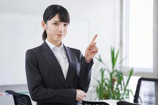Japanese female business woman giving an explanation by pointing at the office