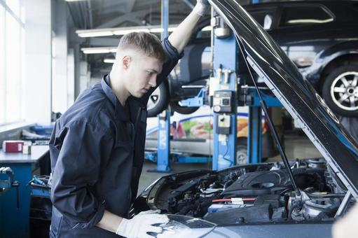 Automobile mechanic who opens the hood and works