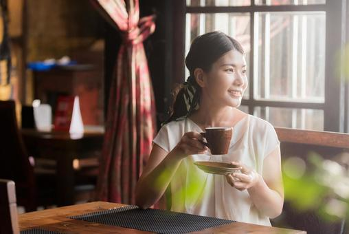 Japanese woman sitting in a restaurant with a cup of hot drink