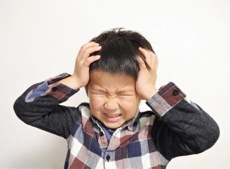 A boy holding his head and hating
