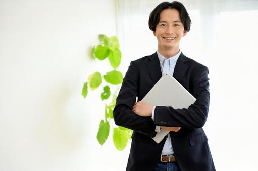 A man standing with a laptop