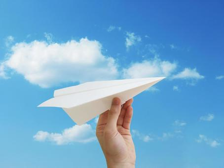 Hand that fly paper airplane and blue sky