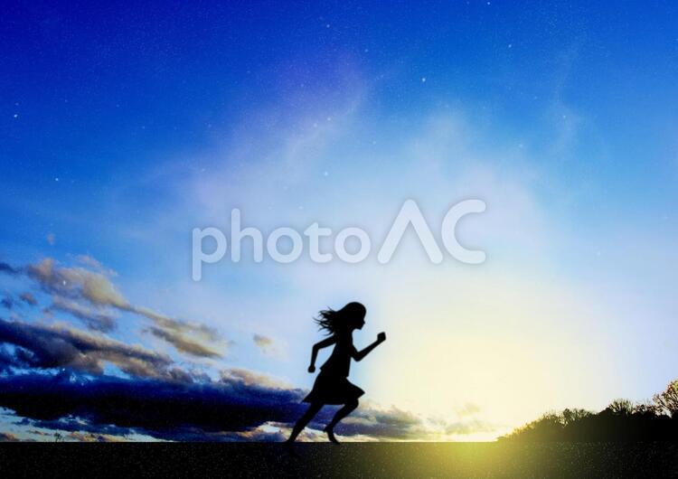夜明けと走る女性のイメージの写真