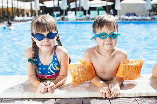 A girl and an boy standing with elbows on the edge from inside the pool 2