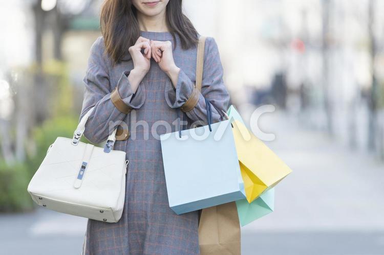 たくさんの買い物袋を抱える女性の写真