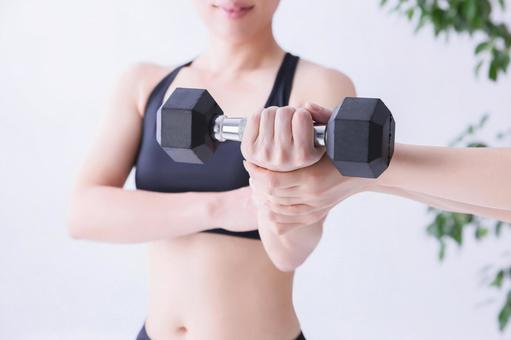 Woman giving a trainer and dumbbells