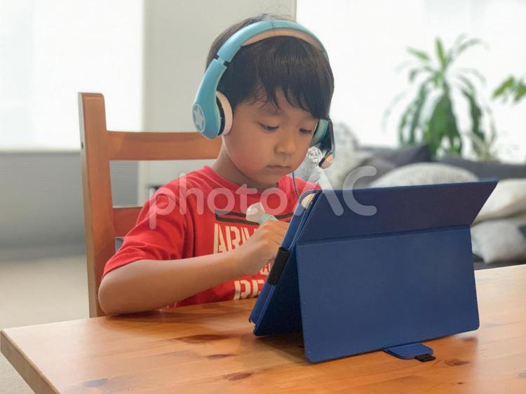 タブレットで勉強する小学生男子 の写真