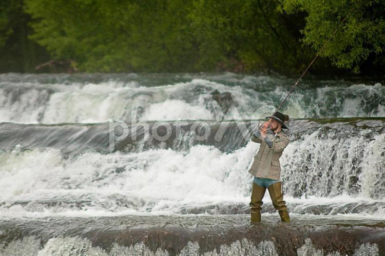 川の堰堤で釣りをする人9の写真