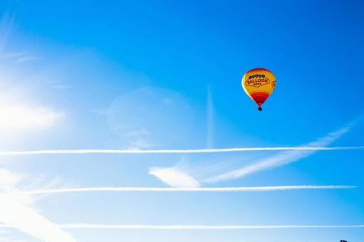 Blue sky and airplane clouds and balloon