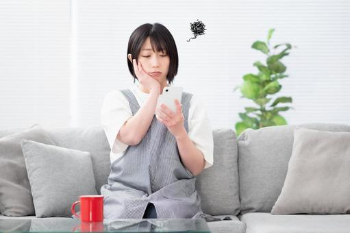 Image of a young woman operating a smartphone between household chores