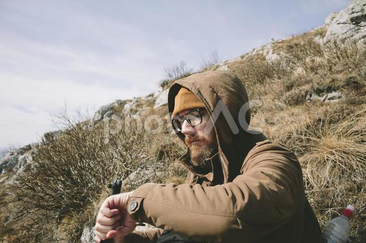 山の斜面に座る男性2の写真