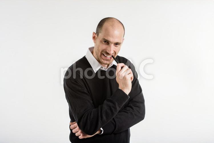 悔しそうにペンを噛む長袖の男性の写真