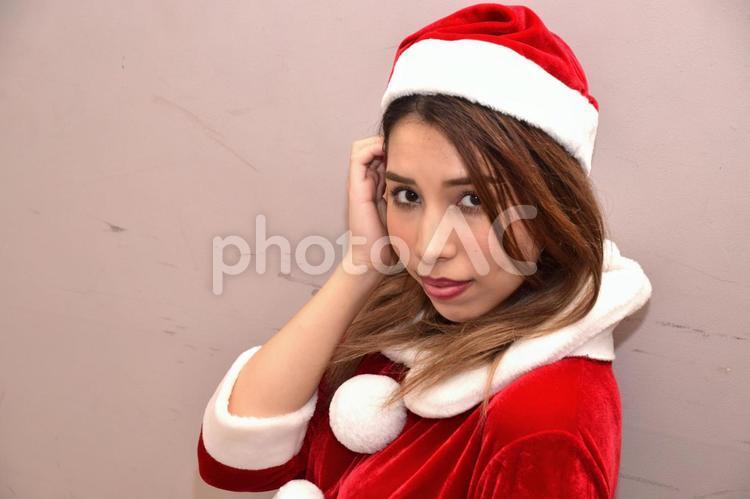 サンタクロースのコスチュームを着てコチラを見つめる彼女の写真