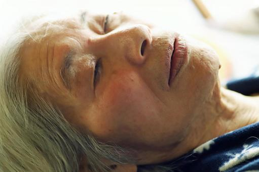 Close-up of the face of a senior woman lying on a nursing bed and closing her eyes
