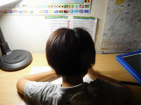 A child (elementary school student) studying at a desk at night