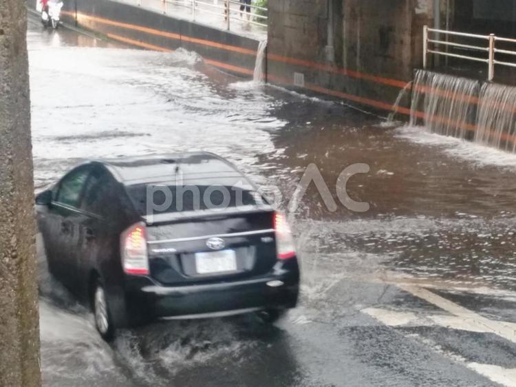 冠水した道路 4(進む自動車)の写真