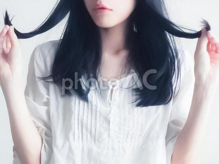 髪をいじる女性の写真
