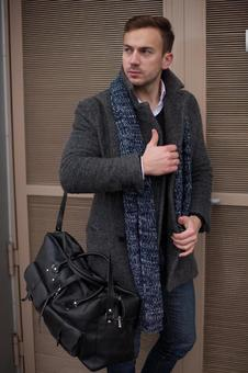 Male model 2 posing with a bag