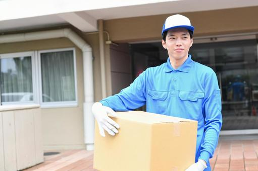 Image of a man wearing work clothes carrying a moving cardboard outdoors