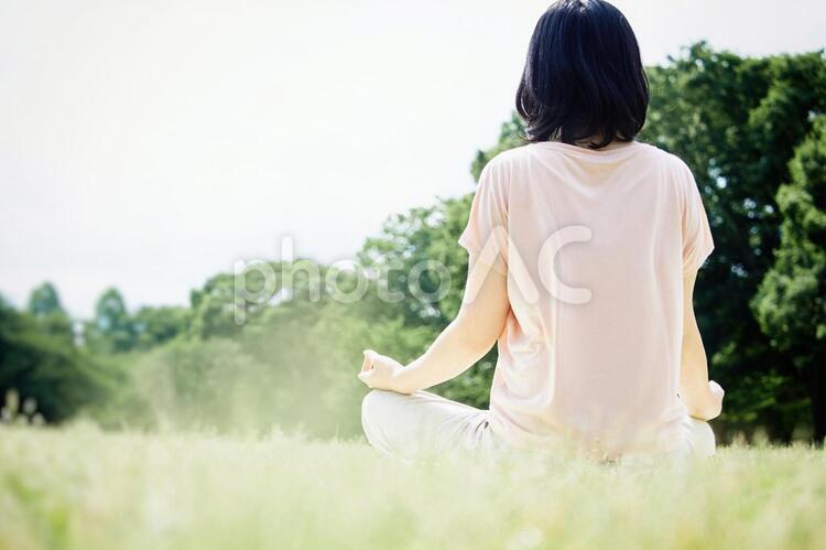 自然豊かな芝生の上で瞑想をする女性の写真