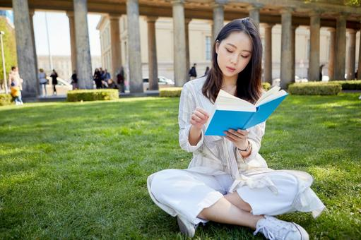 Asian woman reading a book on the lawn 2