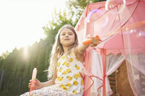 Girl playing soap bubbles in the garden