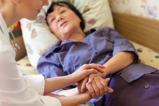 Female doctor taking hands with elderly woman lying in bed 3