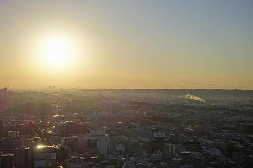 수평선에서 떠오르는 아침 해가 고층 아파트 군을 비추는 풍경