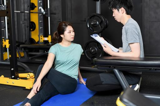 Asian women doing crunches and male trainers assisting