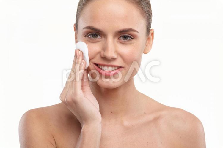 顔にコットンを当てる女性1の写真