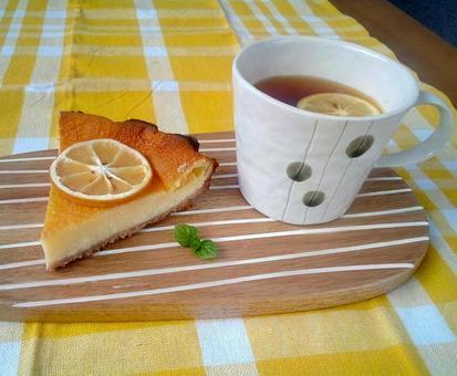 Tea time with baked cheesecake with lemon slices and lemon tea
