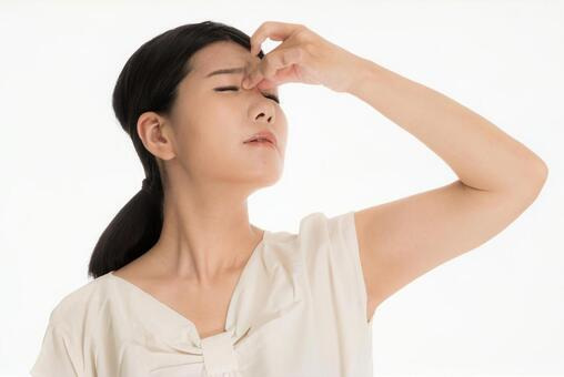 A woman suffering from a medical condition with her hands on her eyes