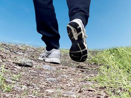 The back of men's shoes walking on a mountain road