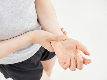 A woman holding her aching wrist on a white background
