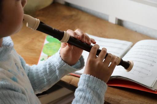 Elementary school girls practicing in homework of music soprano recorder