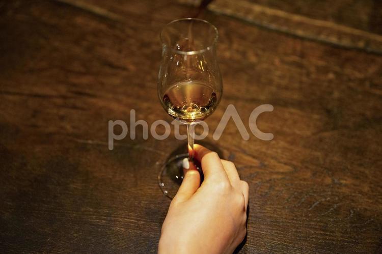 ウイスキーの入ったグラスを持つ手の写真