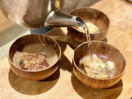 フリーズドライの味噌汁にやかんからお湯を注ぐシーン