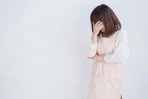 A woman in an apron crying