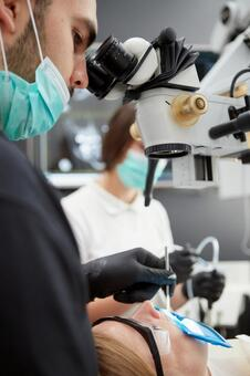 Male dentist with microscope treatment 13