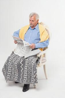Sitting on a chair and reading a newspaper Foreigner Elderly male 1