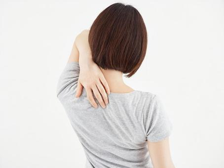 A woman holding a sore shoulder blade on a white background