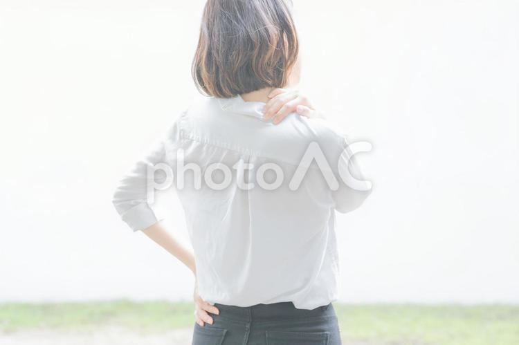 肩こりに悩む若い女性の写真
