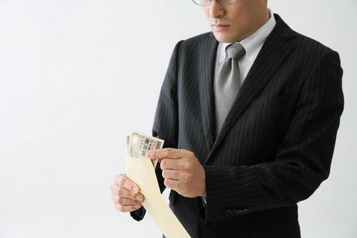 돈이 든 봉투를 보는 남자
