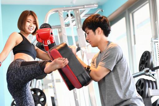 A woman and a trainer kicking a mitt