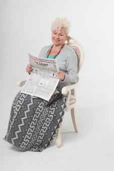 國外老年婦女2讀報紙坐在椅子上