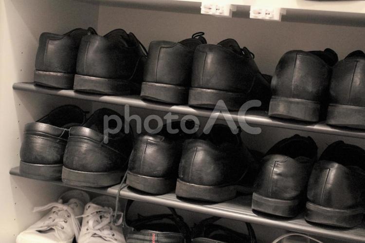 靴箱に並んだビジネスシューズの写真