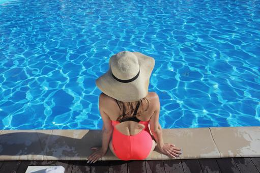 Rear view of a woman wearing a hat on the edge of the pool 2
