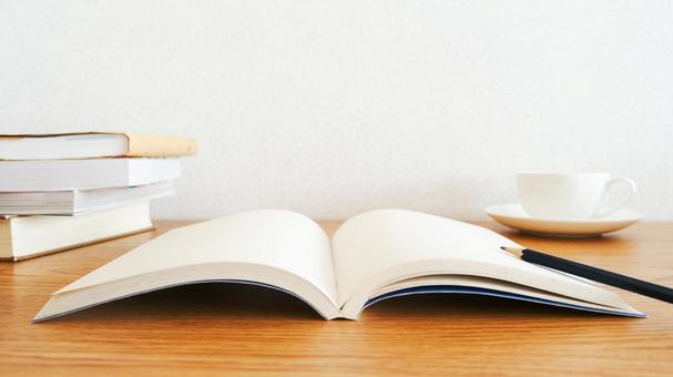 木紋桌子上打開的書閱讀和學習的圖像材料(有咖啡、鉛筆和書籍)