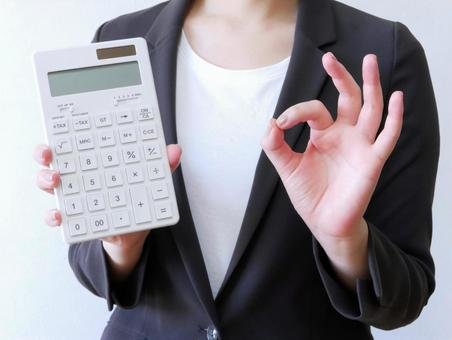 Woman with OK sign holding a calculator